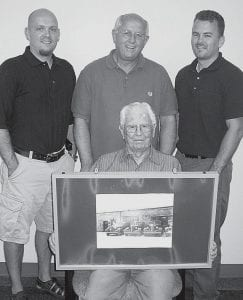 For three generations of Bauses who operate Car 1, an Archbold used car dealership, working with family can't be beat. Ed Baus, seated, holds a picture of the family dealership taken in 1937, when just two cars were displayed in the lot compared to the 30-40 now. I doubt if they sold more than 20 or 25 cars a year,