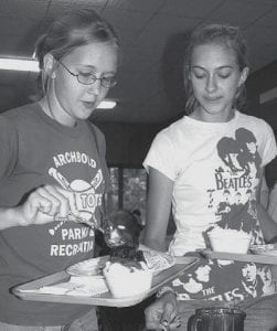 Michal Strawn, left, and Aleah Lambright, 15, Archbold, dish up             ice cream sundaes during the Adriel Ice Cream Social, held Thursday,             July 19, at the Ruihley Park Pavilion.            - photo by David Pugh