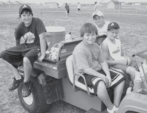 From left, Stetson Wilson, 11, Troy Flores, 11, Dylan Reisser, 13, and Lee Klinger, 12, relax around the school's utility vehicle during football practice Friday, Aug. 3. Wilson, Flores, and Klinger are team managers, while Reisser was helping out. One of their jobs is to keep the team members' water bottles filled and ready.- photo by  David Pugh