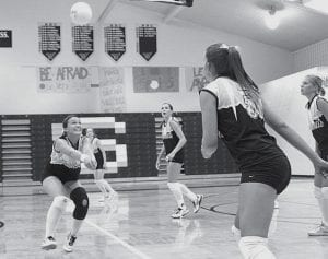 Karina Rohrer-Meck, left, passes the ball as Katie Weber, second from right, sets up to spike. Watching the play develop are Chelsea Schmucker, second from left; Haley Nofziger, center; and Jodi Spotts, right.- photo by Scott Schultz