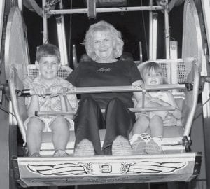 At left, Hudson and Auburn Childs, ages 8 and 5, accompany their grandmother, Mona, on the ferris wheel. At right, Jana Crossgrove Mussard, Powell, formerly of Archbold (AHS Class of 1998) shows