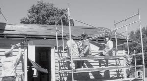 Every project has a start, and ripping off siding had to be completed before the house could come down. From left: Mark Allison, who, with his wife Lisa, is leader of the Groundbreakers youth group, pries at the house while Evan Wyse, Gavin Morton, and Krista Leupp work from the scaffold.