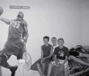 From left, Chandler Stevens, Garrett Morton and Justin Allison appear in the new bedroom they helped build for Chandler. The room is even decorated with LeBron James paraphernalia, just like Chandler wanted.- photo by Alicia Buckenmeyer