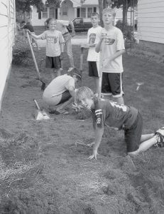 Caroline Vonier and Carson Riehl kneel to use hand tools, while Desi Newman, Bryce Tinsman, and Nick Cassidy, from back to front, are ready to dig with shovels.
