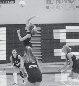 Jessica Henrie goes for the kill while Karina Rohrer-Meck (11), Katie Weber, and Jodi Spotts, from left, cover her.- photo by Mary Huber