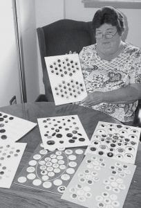 Deborah Layman, Fayette, with some of the buttons she has collected over the years. She said there is so much to learn about the hobby, and she's learning more all the time. - photo by David Pugh