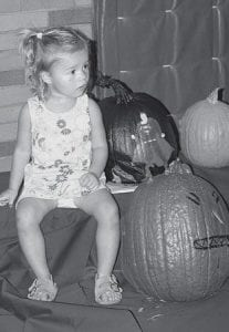 At left, Holland Klopfenstein, 2, Pettisville, is a cute little pumpkin among a bunch of gourds at the Pettisville Pumpkin Fest, Friday, Oct. 5. She sat down for a few minutes and watched the activities happening in the Pettisville gymnasium, including a bake sale, face painting, games, and an auction of decorated pumpkins. At right, William Fenton, 6, Pettisville, poses with some pumpkins that were decorated by Ms. Enderle's sixth grade class.- photos by Mary Huber