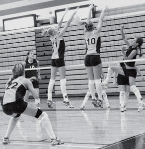 A spike meets the forearm of Emily Snyder (11) as she and Stacy Wyse (10) go up for a double-block in volleyball action, Saturday, Sept. 29. The Streaks are 19-1, 6-0 in the NWOAL with two regularseason games remaining.- photo by Scott Schultz