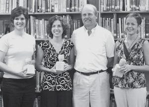 The Pettisville School Board presented carved wooden apple trophies    to several teachers in recognition of earning master's degrees.        From left: Marla Miller; Jodi Crossgrove; John King, board president;          and Lynne Hoffmire.- photo by D.J. Neuenschwander