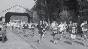 A total of 117 competitors thunder out of the Lockport Covered Bridge, at the start of Bridging The Gap to Heart Health, a running and walking event, Saturday morning, Oct. 6. There were 72 runners entered in the five kilometer, and 10 kilometer run, and 45 entered in the five kilometer walking competition. Participants faced extreme heat and humidity.- photo by David Pugh