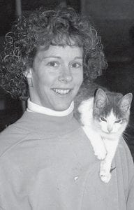 Tracy Knisley, with one of the 40 cats who live on the family dairy farm. Just like the cows, each cat has a name.- photo by David     Pugh