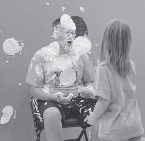 Top, Bekah Frey, a fifth grader at Pettisville Elementary School, throws a whipped cream pie at Jason Waldvogel, elementary principal, during a student assembly Friday afternoon, Oct. 19. Below, Waldvogel sweetly smiles at the cheering children. The chance to throw pies at the principal was a reward for 34 students who each raised more than $100 in donations toward Friday's