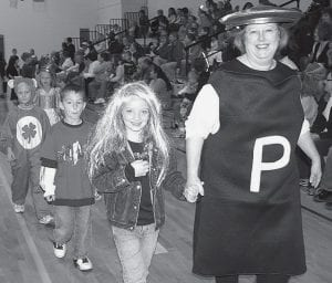 Each year, students and teachers at Archbold Elementary School wear their Halloween costumes to school and parade for their parents, friends, and relatives. LouAnn Kleck, first grade teacher, adds a little