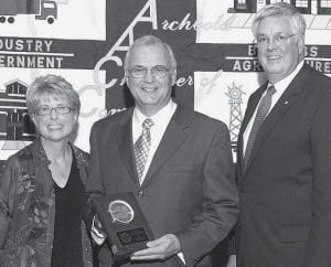 Debbie David, left, outgoing Archbold Area Chamber of Commerce president, and Paul Siebenmorgen, incoming president, right, present Lynn Aschliman, Archbold 2007 Citizen of the Year, a plaque commemorating the award. Aschliman heaped praise on the Archbold community, stating that without an outstanding community, there would be no citizen of the year. - photo courtesy Royal Images