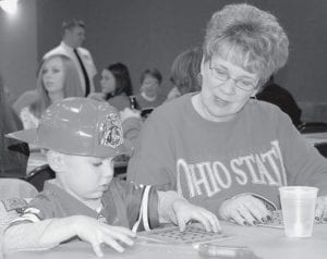 Parker Von Deylen, 4, covers the called number on his bingo card while grandmother Linda Von Deylen watches at the Archbold-German Township Fire Department Feather Party, Saturday, Nov. 17. Parker's grandfather and Linda's husband, Robert Von Deylen, was a retired fire chief on the Ridgeville Township Fire Department before he died last year. More than $8,000 was raised toward a new thermal imager.- photo by Mary Huber