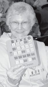 Bingo! Jean Geesey, Archbold, holds up a winning bingo card at the Archbold Fire Department Feather Party, Saturday, Nov. 17.- photo     by Mary Huber