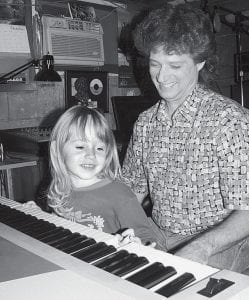 Steve Zaborniak holds his three-year old daughter Emma while she looks over the keyboard in his basement studio. Zaborniak has written songs for radio and television commercials and entered songwriting contests. One of his songs earned him a television Emmy nomination.- photo by David Pugh