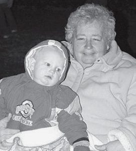Becky Short, Archbold, and 10- month-old grandson Caden Leininger, Fayette, stay warm while waiting for the Archbold Parade of Lights.- photo by Mary Huber