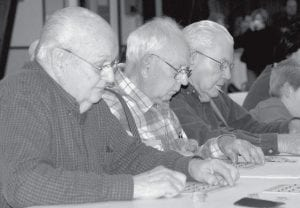 Dean Short, Archbold, Morris Kruse, Ridgeville Corners, and Luther Reinking, Wauseon, from left, concentrate while looking for bingos during the Ridgeville American Legion Feather Party, Friday, Nov. 16.- photo by Mary Huber