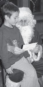 Gibson Burkholder, 7, Archbold, shows Santa Claus a list of Christmas wishes prepared by his sister Nolyn, 9 1/2, who was ill and could not sit on Santa's knee. Santa visited Ruihley Park Pavilion, Friday, Dec. 14. Santa's visit was sponsored by the Archbold Parks and Recreation Department. Dozens of youngsters were lined up to see Santa that night.- photo by David Pugh