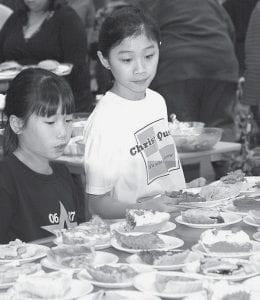 Tessa Waidelich, 9, left and big sister Claire, 12, have a big decision to make at the dessert table during the Fairlawn Auxiliary auction, Friday, April 4. The sisters are from Pettisville.- photo by Mary Huber