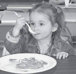 Almost-three-year-old Brayton Huffman enjoys pancakes at the Archbold Fire Department pancake and sausage breakfast, Sunday, April 6, at Ruihley Park Pavilion. Kyle Brodbeck, an AFD firefighter, said there was a good turnout. It raised $3,000. All proceeds go to the American Cancer Society Relay for Life.- photo by David Pugh