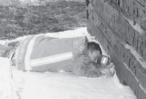 Kyle Brodbeck, Archbold Fire Department firefighter, lays in a puddle of water and fire-suppressing foam to spray foam under a small log cabin, Monday, April 7. It was used for storage at Sauder Village. A rekindled grass fire caused the blaze, which did minimal damage to the building.- photo by David Pugh