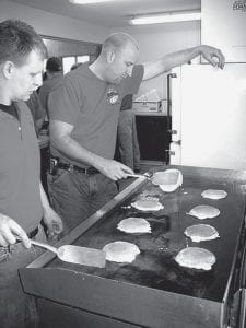 David Eicher, left, and A.J. Schroeder, Archbold Fire Department firefighters, demonstrate their culinary skills by flipping pancakes during Archbold Fire Department pancake and sausage breakfast, Sunday, April 6 at the Ruihley Park Pavilion. The event raised money for the fight against cancer, which goes to the American Cancer Society Relay for Life program.- photo by David Pugh