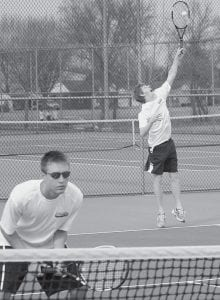 Darin Bontrager serves while doubles partner Jacob Lange stands at the net waiting for a return in Archbold's match with BG.- photo by  Scott Schultz