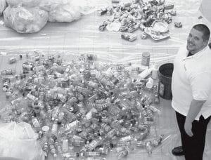 Collin Doolittle, plastics instructor at Northwest State Community College, stands with a pile of recyclable plastic bottles that was sorted from NSCC trash during a