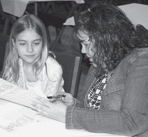 Stacie Britsch, right, explains the rules of the Archbold Rotary Club 450 Night reverse raffle to Marissa Fryman, 9, Archbold, Friday, April 18, at Founder's Hall. The event raises scholarship funds for Archbold High School graduates.- photo by David Pugh