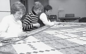 From left, Melda Richer, Donna Smith, and Karen Nafziger work on the 2008 Pettisville Friendship Days quilt, to be sold during Pettisville Friendship Days, Friday through Sunday, June 27-29. A total of 56 quilters from Pettisville completed the queensize, 96 by 114 inches, quilt. The work took about 420 hours and used 625 yards of thread. Nafziger and Char Roth, 2008 Friendship Days quilt chairmen, chose the pattern, Caramel Latte. It's pieced in green-patterned fabrics and beiges, with red, brown, and black accents. The quilt will be sold Friday, June 27. Friendship Days is held every other year.- courtesy photo