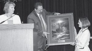 Todd and Sabrina Grisier present a lighthouse print to Melanie Whitlock, hospice coordinator, Hospice-The Caring Way of Fulton and Williams Counties, at the Beacon of Hope benefit, Thursday, April 24. The lighthouse is a symbol of the hope offered by Hospice and the eternal light that burns within each human. Below, the Grisiers accept the