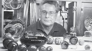 Mark Matthews with some of his glass items in his Sauder Village workshop. He is known for his glass spheres.- photo by Rita Bilen