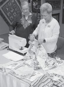Above, Verna Grant, Hudson, Mich., left, watches as Pat Hilbert, a Sauder Village volunteer, demonstrates a sewing technique during the Sauder Village annual quilt show, held April 29 through May 4 at Founder's Hall. Grant, herself a quilter, has attended every show, and often finds ideas for the quilts she makes. At right, Chris Holland, Pettisville, quilts during the show. She is one of the few who does not use a thimble. Instead, she uses her fingernails to push the needle. This year, 5,333 guests visited the quilt show, up about 2.3% from last year's attendance.- photos      by David Pugh