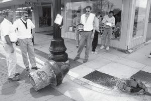 Representatives of the Archbold Engineering Department look over the bell bollard which was pulled from its underground concrete foundation by a semi truck, Monday afternoon, May 5. From left are Chuck Lehman, project representative, Bob Seaman, village engineer, and Jon Block, engineer. Behind Block, from left, are Daniel Beck, Archbold, Tera Rogers, Archbold Police officer, and Randy Nofzinger. Beck and Nofzinger witnessed the incident. The driver of semi rig said he did not notice his truck had hit the bollard.- photo by David     Pugh