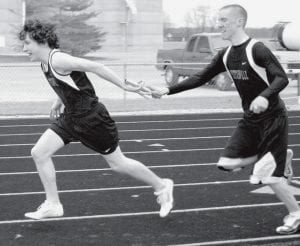 Chris Matthews receives the handoff from Chase Gingerich in track action earlier this season.- photo by D.J. Neuenschwander