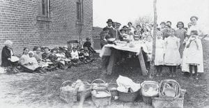 It was a day to picnic at the Moine country school in 1915. Picnic baskets of tasty food dishes covered the buffet table displayed over a white tablecloth. Osee Buehrer, far right, hand on hip, was teacher of the one-room school at the corner of West Lutz Road and Co. Rd. 24. Anna Mae Short, back row, daughter of Joe B., is peeking around the young tree. No others identified.- antique photograph          from the collection of Isabelle Pursel, Archbold