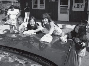 Kids and grownups were working at a fund-raiser car wash for the Good Shepard Mennonite Church, Saturday, May 10. Tony Quintanilla, 11, far left, handled advertising. Scrubbing a car, from left: Zach Rocha, 7, Kitana Espinoza, 10, Selena Espinoza, 12, and Zoey Quintanilla, 7, Archbold.- photo by David Pugh