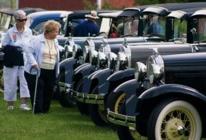 More than 70 antique autos visited Sauder Village, Saturday, May 17. Top: Carole Quickery, left, Huntington, Ind., and Mary Hasty, Ft. Wayne, Ind., observe a row of Model A Fords. Bottom Left: American flags were a popular decoration back in the day.