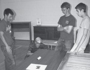 From left: Jackson Beck, an AHS junior; Galen Plank, Pettisville; Daren Bontrager, an AHS senior; and Brian Plank, a Pettisville High School sophomore, look over a desk made of walnut by Paul Schoenhals, an AHS freshman, during the Friday night, May 16 industrial arts show. The desk was one of many projects on display.-  photo by David Pugh