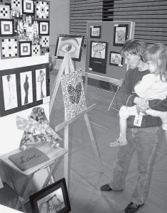 Lynette Roehrig, Archbold, and her daughter Alison, 3, look over student art displays Friday, May 16, during the Archbold High School Spring Art Show. Hundreds of items, representing several different styles, were on display.- photo by David Pugh