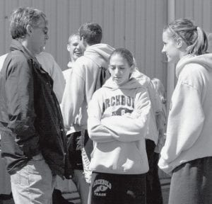 Mike Wachtmann, AHS assistant track coach, discusses strategy with Trisha King and Katrina Gobrogge. Gobrogge was the league champion in the 800 at last week's NWOAL meet.- photo by Mary    Huber