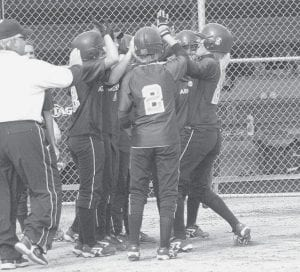 Above, teammates and coaches greet Dani Newman at home plate after the Blue Streak senior hit a three-run blast over the left field fence in the fifth inning against Wauseon. At right, Newman smiles as she rounds third base and heads for home. Archbold won a share of the NWOAL title with an 8-5 victory over the Indians; the Streaks share the title with Evergreen.- photos by  Scott Schultz