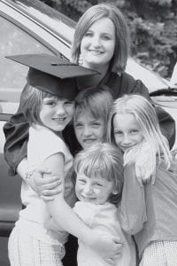 Holly Rychener, a member of the newest group of Pettisville High School alumni, receives congratulations from her nieces following the PHS graduation ceremony, Sunday, May 25. Middle row, from left: Samantha Boger (with cap), Kenzie Morgan, and Jocelyn White. At the front of the group is 3-year-old Taylor Boger. The Bogers and Morgan are from Wauseon. White traveled to Pettisville from Virginia to see her aunt graduate.- photo by D.J. Neuenschwander