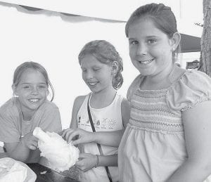 Top: Blue cotton candy was a tasty treat for Johanna and Brooke Roth, rural Archbold, and Natalie Hoffmier, Wauseon. The variety of things to do on the midway at the Black Swamp Benefit Bazaar helped set another new attendance record for the annual fund-raiser.