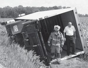 Shane Myers, a Fayette Fire Department rescue worker, left, and Andy Brodbeck, Archbold Fire Department chief, step out of the body of a truck that rolled onto its side after driving off the right side of St. Rt. 66 north of Co. Rd. J. The driver was uninjured.- photo by Mary    Huber