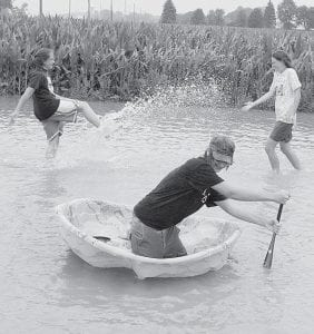 After more than two inches of rain fell on the Archbold area Wednesday night, July 2, these youngsters were out frolicking in the floodwaters the next day. In the background, Genny Lehman, 13, tries to splash 13-year-old Tressa Parsley, while in the foreground, Colin Lehman, 15, uses a baseball bat to try to paddle a kid's swimming pool turned boat. The trio were in the Lehman's front yard along US20A near Burlington; Parsley is from the Burlington area.- photo     by David Pugh