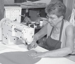 Trudi Short sews parts to make a new seat cushion for an Allis-Chalmers tractor, in the correct orange and white colors. Y&F Cushions, founded in Archbold in 1956, recently moved to Wauseon.- photo by  David Pugh