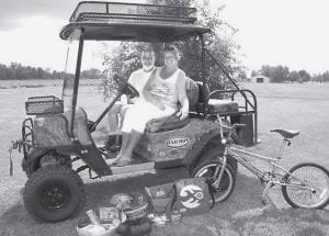 Laurie and Terry Rohlf sit aboard the $7,000 all-electric all-terrain vehicle Laurie won from entering a contest. In front of the ATV are just a few of the other prizes she has won. Laurie said she enters about 10 to 15 contests a day.- photo by Rita Bilen